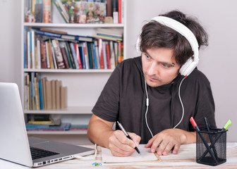 E-Learning. Man with headphones sydying by Laptop