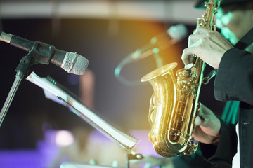 The saxophone was held by the hands of musicians.