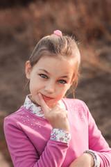 autumn portrait of beautiful kid girl walking outdoor in pink dress. Rural natural scene.