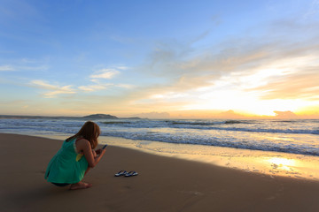 woman travel enjoy take a photo on the beach with sunrise