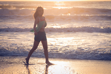 woman walking on the beach, sunshine in the morning