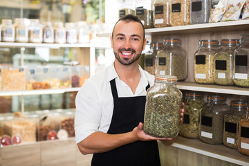 Male seller with jar of dried herbs