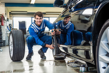 Confident Mechanic Changing Car Tire In Garage
