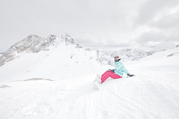 Young sitting woman with snowboard