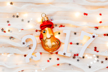 Christmas and New Year background with numbers 2017, decorations and light bulbs. Symbol of year - golden fiery rooster.
