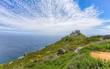 View of Cape Finisterre, Galicia, Spain with the lighthouse under a cloudy blue sky