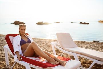 Beautiful blonde girl in swimwear lying on chaise near sea.