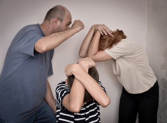 Domestic violence: Young boy bending down and covering his head with his hands while the father is threatening his mother. Focus on the young boy.
