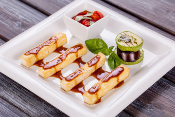 cheese sticks with sauce and vegetables