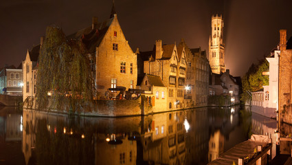 Reflections in the canals of the medieval town of Bruges by night, Belgium