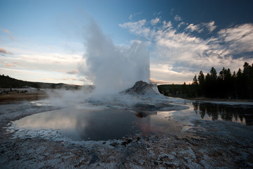 Castle Geyser errupting at sunset in Yellowstone National Park, USA