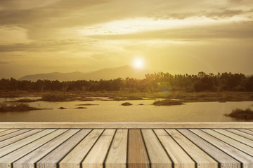 Empty top wooden table and sunset moment at mountain background.