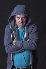 Portrait image of a mature man wearing a hoodie and looking intimidating