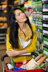 Thoughtful woman standing with shopping cart in grocery section