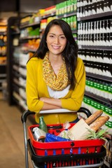 Woman standing with shopping cart in grocery section