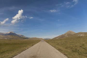 Straight mountain road across a green filed. Blue sky with clouds in the background