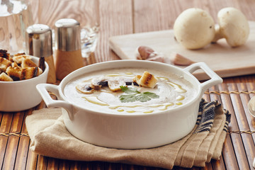 Mushroom cream soup on a table, with bread, garlic, and raw mushrooms on a white chopping board. Salt and Pepper on the table..