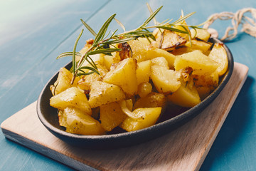 roasted potatoes iwith onion and rosemary in a cast iron pan over a white chopping board on a blue table