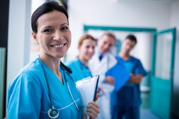 Portrait of smiling surgeon holding a clipboard in corridor