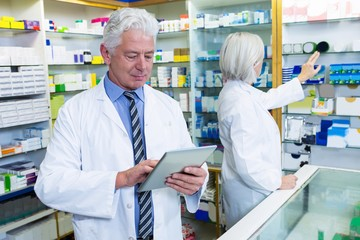Pharmacist using digital tablet and co-worker checking medicines