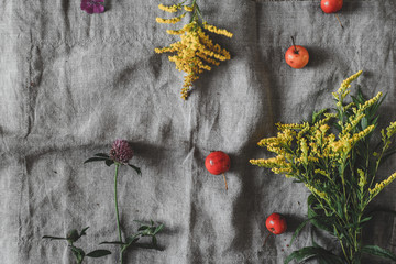 Autumn flowers and apples on the grey cloth top view