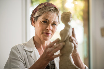 middle-aged woman who shapes a statue in her home