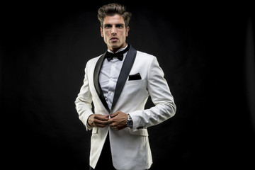 Handsome, elegant man in a white suit tuxedo with bow tie around