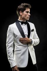 elegant man in a white suit tuxedo with bow tie around his neck