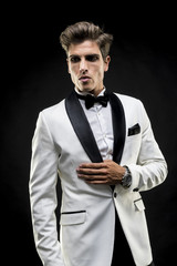 elegant man in a white suit tuxedo with bow tie around his neck