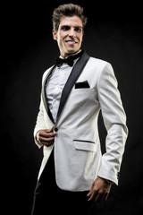Party, elegant man in a white suit tuxedo with bow tie around hi