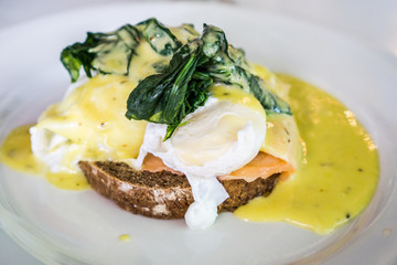 Egg benedict on brown homemade bread, topping with green spinach, smoked salmon and yellow cream sauce