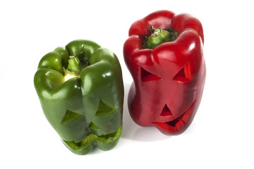 Food art creative concept. Halloween scary face carved into green capsicum vegetables isolated over a white background.
