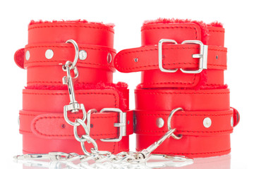 Pair of a red color leather handcuffs isolate on white background with clipping path.