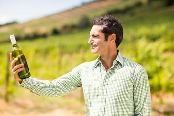 Smiling vintner looking at bottle of wine