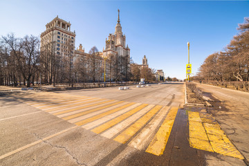 Wide angle view of long avenue of spring sunny campus of Moscow University with yellow zebra crossroad