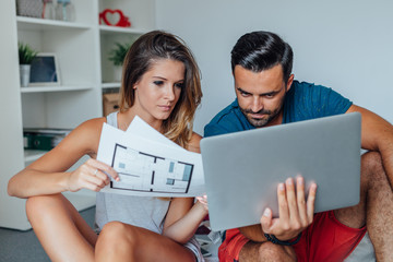 Young couple is using laptop pc while woman is holding architect