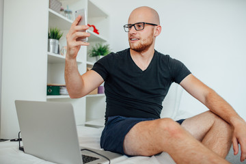 Young man is taking a selfie while sitting on bed. Home backgrou