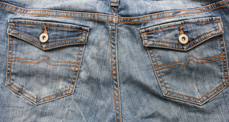 Blue denim jean pants back pockets with buttons texture fabric close up modern urban lifestyle background with empty copyspace casual style clothing fashion for woman man teenagers