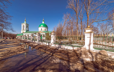 Wide angle view of molten snow, tree shadows and orthodox church in the park of spring sunny campus of Moscow University