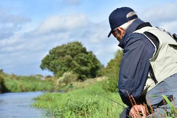 Flyfisherman fishing from riverbank, Irish countryside