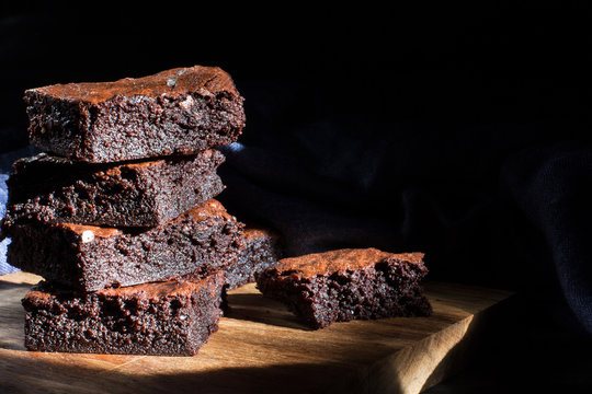 Chocolate brownie on the black background, side view, selective focu