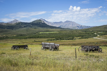 horizontal image of three old vintage wooden wagon with wooden wheels sitting behind a barbwire fence in the meadow with a beautiful landscape and mountains in background in summer.
