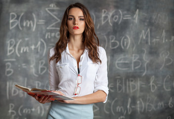 young smart woman holding book in her hands  near blackboard with math calculations