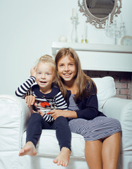 two cute sisters at home interior playing, little happy smiling girl in interior, lifestyle modern real people concept