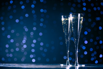 Wall Mural - Two glasses of champagne on dark bokeh background