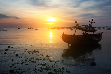 Silhouette natural background of small fishing boats moored beached on the beach during time the sunset and the beautiful natural of the colorful sky at BangPhra beach , Chonburi province in Thailand