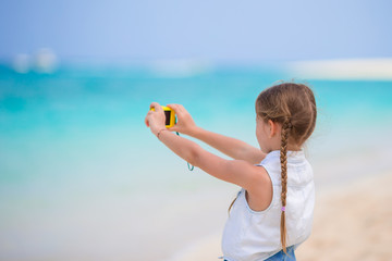 Little girl making video or photo of tropical beach with her camera for the memory