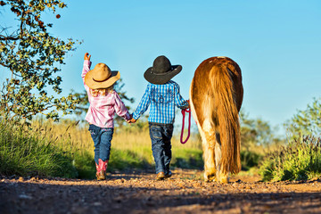 Little cowgirl and cowboy with pony Wall mural