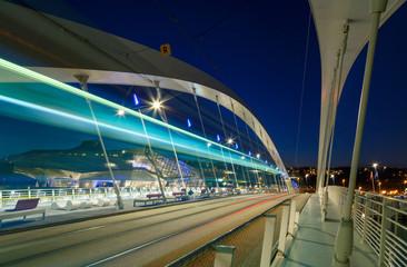 Tram speeding over a bridge in Lyon at dusk.
