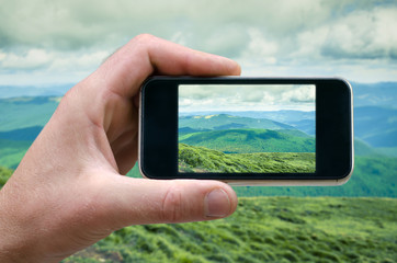 phone in a man's hand, mountain landscape photographs on your smartphone, side view, selfie